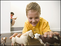 Boy plays with animal figurines