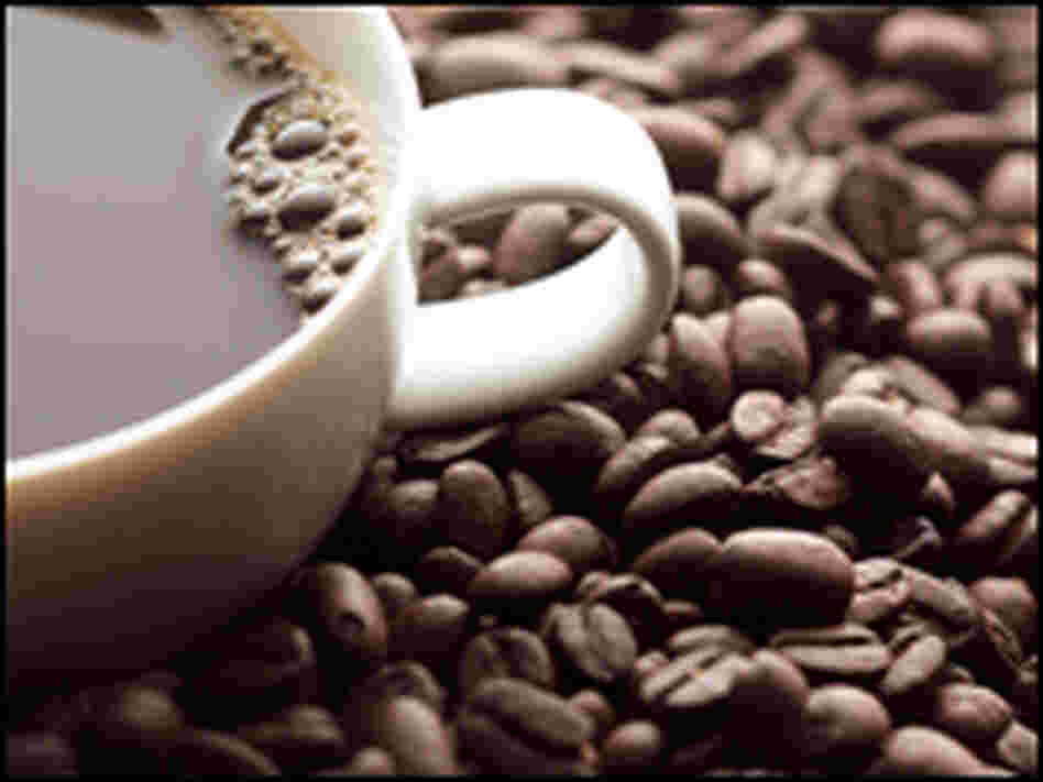 A cup of coffee sits on coffee beans.