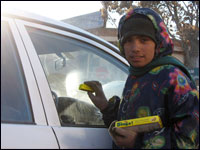 Malayeh, 11, tries to hawk gum to a driver on a busy street in Kabul.