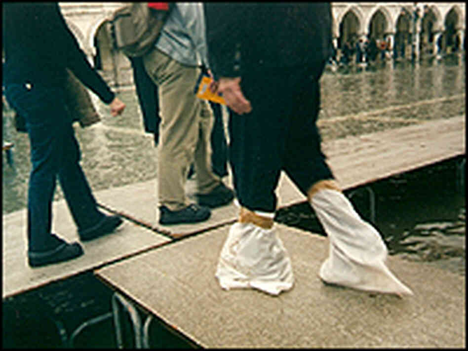 Venetians walk on raised walkways.