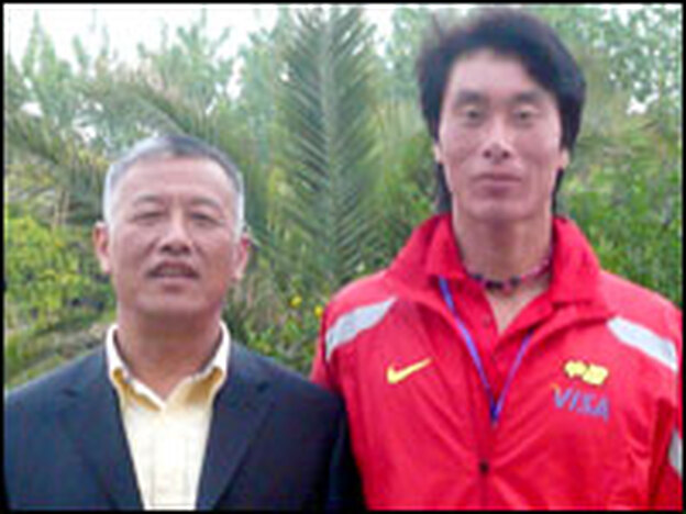 Chinese rower Zhang Liang (right) stands with the national rowing team coach Zhou Qinian.