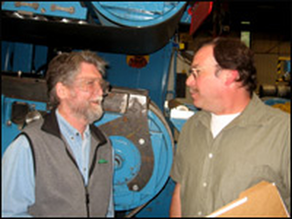 Blair Hamilton (left), director of Efficiency Vermont, speaks with Alan Landry, facilities manager for a factory owned by Hazelett Strip-Casting Corp.