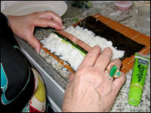 "Miura creating a ""maki"" sushi roll, with sticky rice and Spam, wrapped in nori, the flat, dry seaweed wrapping."