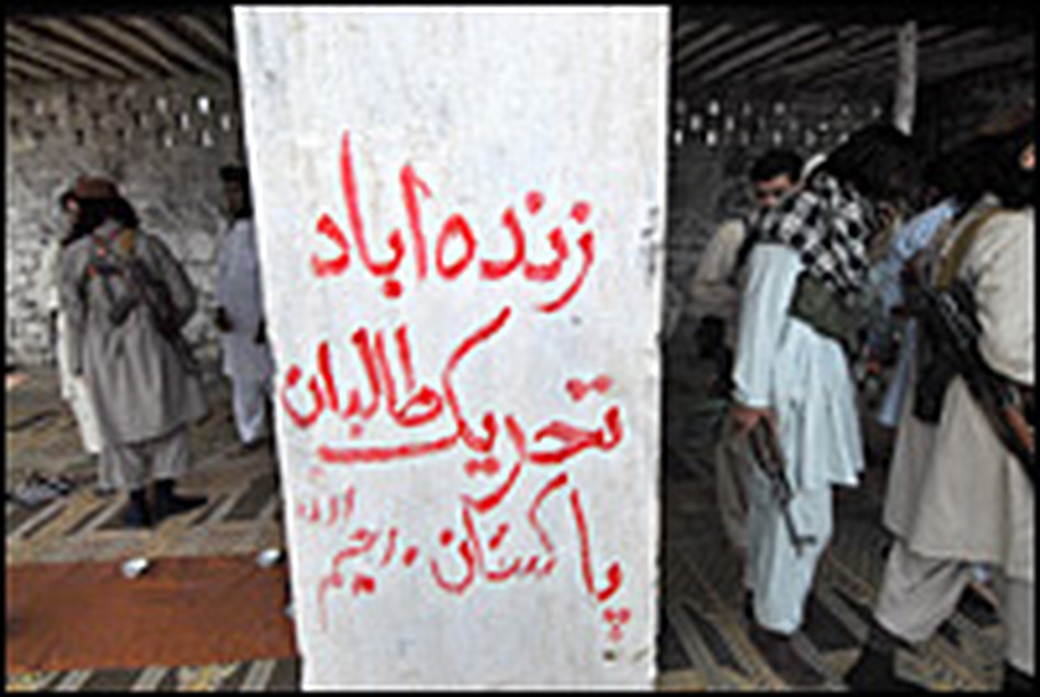 """Armed militants of Tehrik-e-Taliban Pakistan gather around graffiti that reads """"Long Live Tehrik-e-Taliban Pakistan"""" at a camp in a Pakistani tribal district of Mohmand Agency on July 21."""