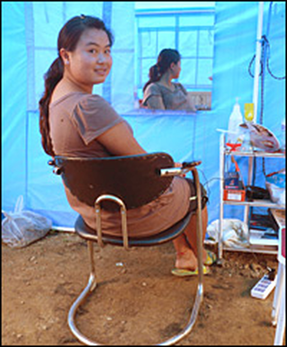 Li Jin waits for customers at her tent beauty salon. She had just invested $15,000 in a new beauty salon in Beichuan, China, due to open the day the earthquake struck.