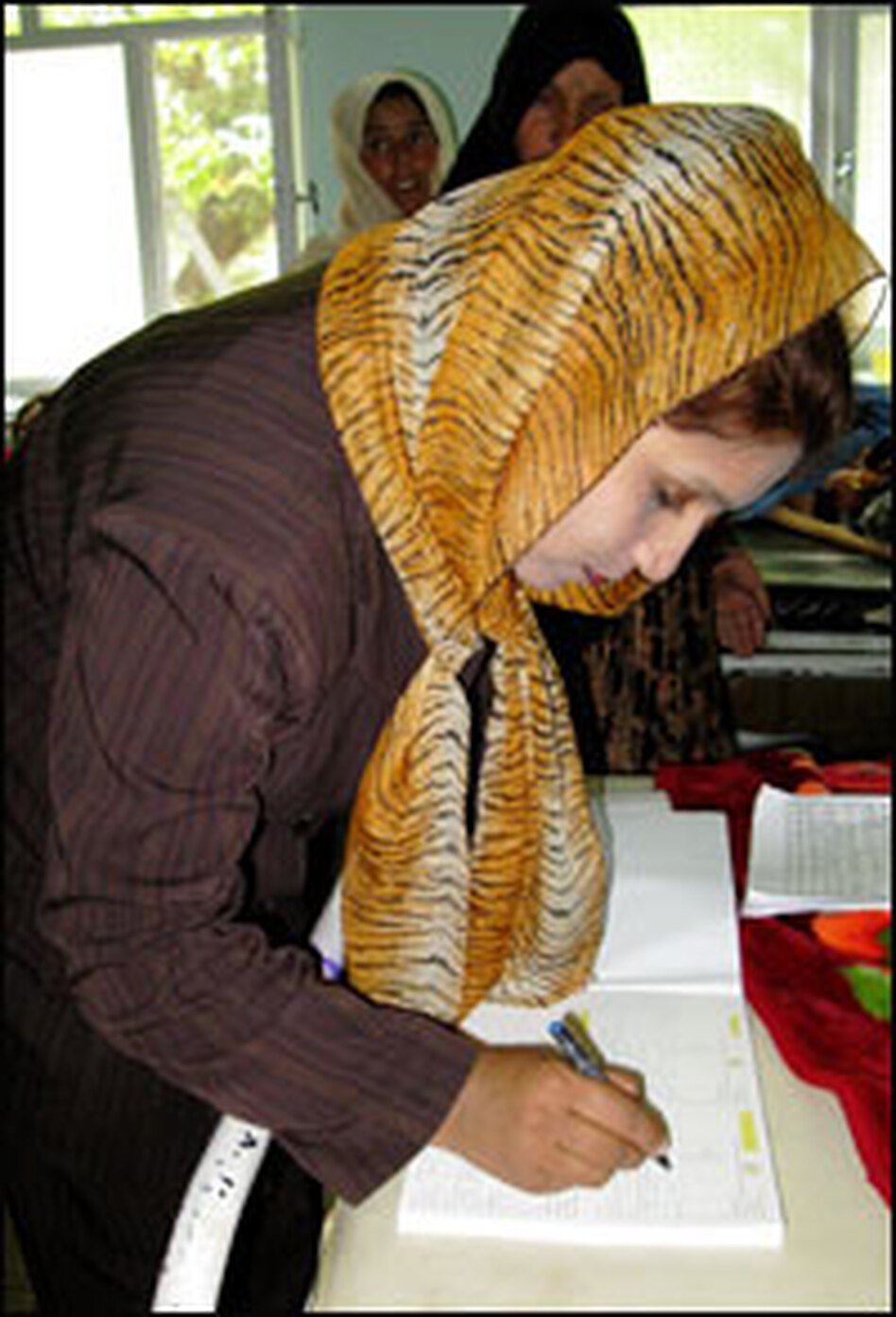 Hospital worker Mahbooba fills out a birth certificate for a newborn baby in Kabul.