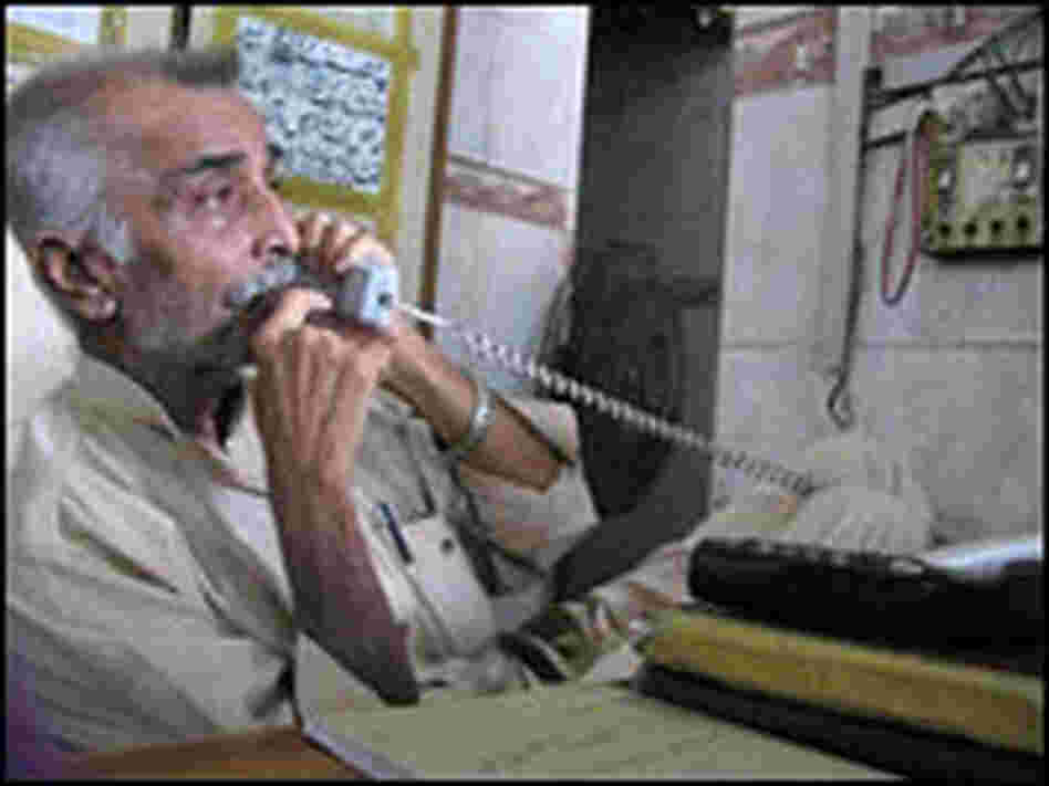 Anwar Kazmi talks on the phone at the Edhi Ambulance Service headquarters.