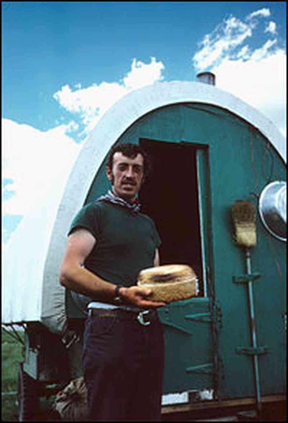 A herder holds freshly baked bread outside his wagon.