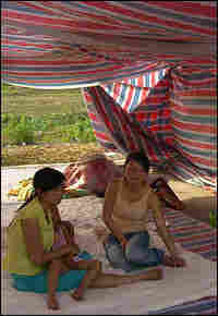 Sisters Chen Huayu, holding her 3-year-old daughter, and Chen Xiaoli sit in a makeshift tent.