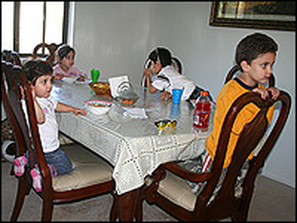 Rawa Bahou's three children sit with their cousin (right) for dinner. Bahou and her children live share a two-bedroom apartment in suburban Detroit with her brother-in-law, his wife and their two children.