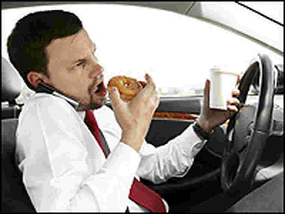 A man juggles his cell phone and a doughnut while driving