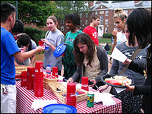 A group of UVA students serve themselves food from a table.
