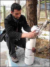 A specialist with the National Environmental Protection Agency sets up an air pollution monitor