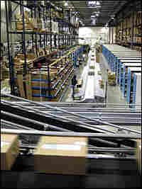 Conveyor belts full of merchandise in warehouse.