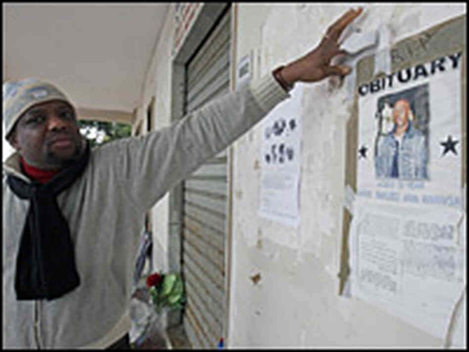A man points to a poster showing a portrait of Karim Yabuku.