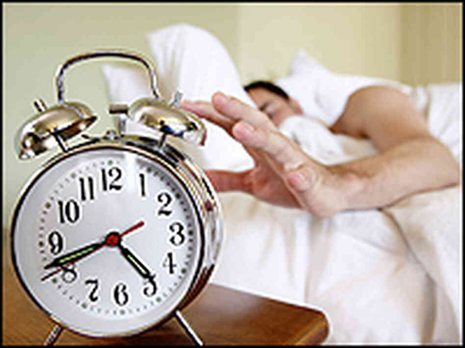 A man reaches to snooze his alarm clock.