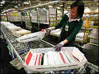 Postal Service worker sorting mail