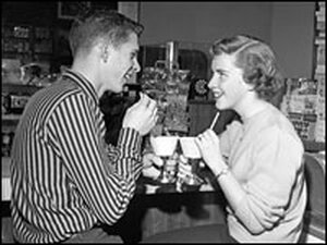 A young man and woman have drinks at the soda fountain on a date.