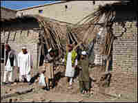 Pakistani tribesmen gather at the site of a missile attack in North Waziristan