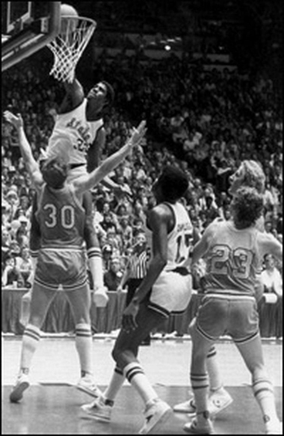 Magic Johnson dunks the basketball against Bob Heaton of the Indiana State University Sycamores while Larry Bird (standing in front of No. 23) watches.
