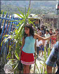 A girl waits as a church group passes out blankets and clothes at the Gerardo Barrios squatter camp