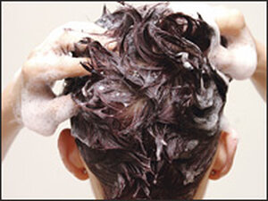 A woman lathers up her hair with shampoo.