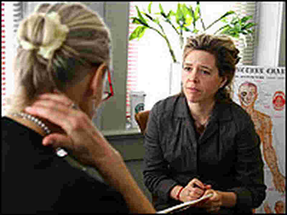 Acupuncturist Kate Yonkers consults with a patient who is having trouble with shoulder pain.