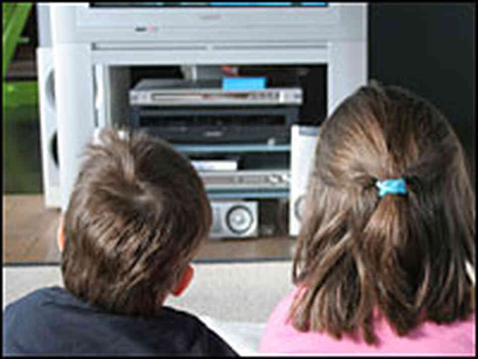 Two children watch television