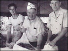 Men wrap beef in cheesecloth at a sheriff's barbecue in Los Angeles.