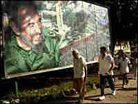 Cubans pass by a poster of President Fidel Castro on their way to work Tuesday.