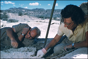 Dr. Louis Leakey lies on the ground to dig,  while his wife Mary sits and digs next to him. The two were at Tanzania's  Olduvai Gorge on a National Geographic expedition.