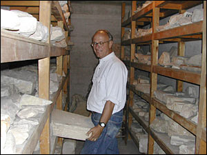 Archeologist John Camp inside a storeroom and holding a stone tablet from about 300 B.C.