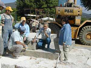 Chief mason Yannis Arbelius talks to workers as they hunch on stone slabs at Nemea.