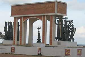 An arch with metal sculptures on either side that is meant to recall Africans sent into slavery