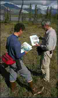 Expedition graduate student Martin Robards, left, and Schaller use old photos to find the campsite
