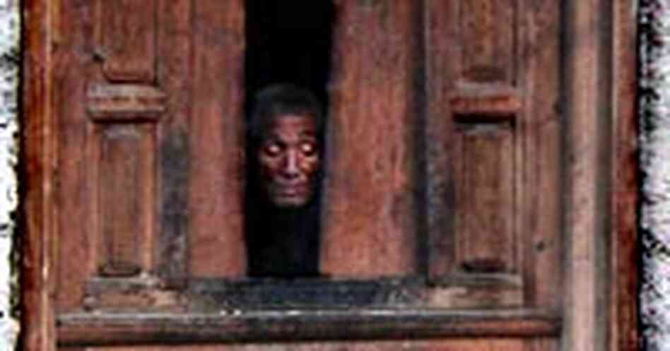 A Gebu village resident peeks from his window down at the street below.