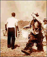 A circus clown carries a bucket of water amid attempts to put out the fire.
