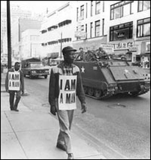 Striking sanitation workers march in Memphis in 1968, escorted by the National Guard.