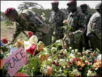 Kenyan police visit a memorial for those killed in post-election violence.
