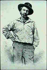 Walt Whitman in 1854, wearing a flat-topped hat, arms akimbo.