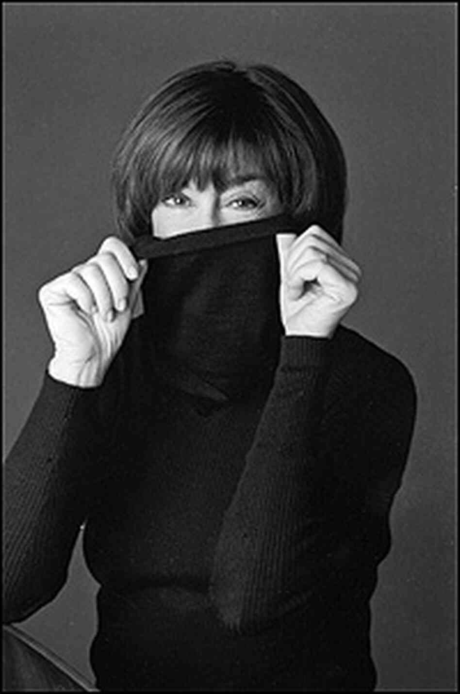 Photo of Nora Ephron hiding her neck inside a black turtleneck sweater.