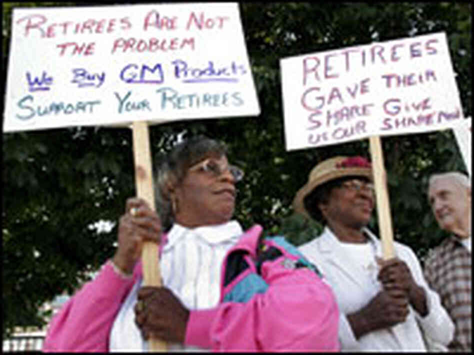 Retired United Auto Workers union members picket the opening of the contract negotiations.