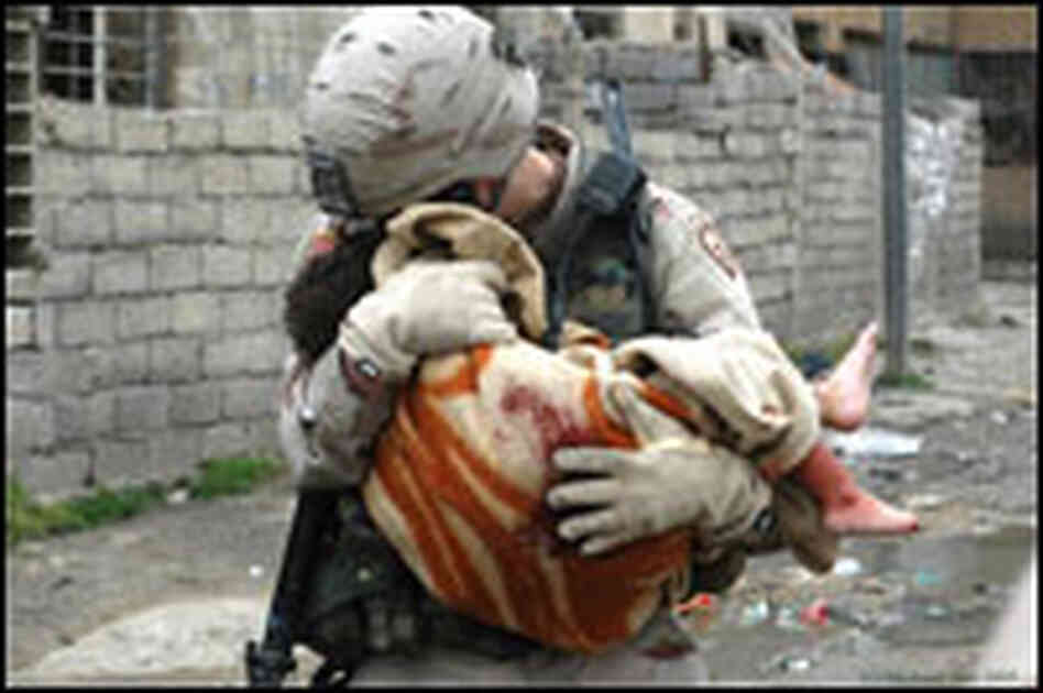 A soldier cradles the body of a young Iraqi girl killed by a car bomb