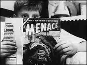 Boy reading comic book looks shocked.