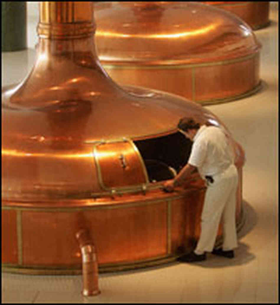 A worker checks the brew in giant copper vats at the Prazdroj brewery in Pilsen, Czech Republic.