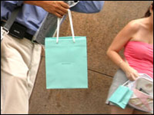 Shoppers walk with Tiffany's bags.