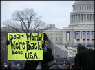 "A man holds a sign at Barack Obama's inauguration that reads ""Dear World, We're Back, Love U.S.A"""