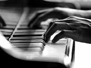 Hands playing on a piano.