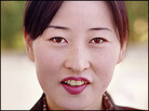 This young woman works at a souvenir and snack kiosk on the highway near Kaesong, North Korea.