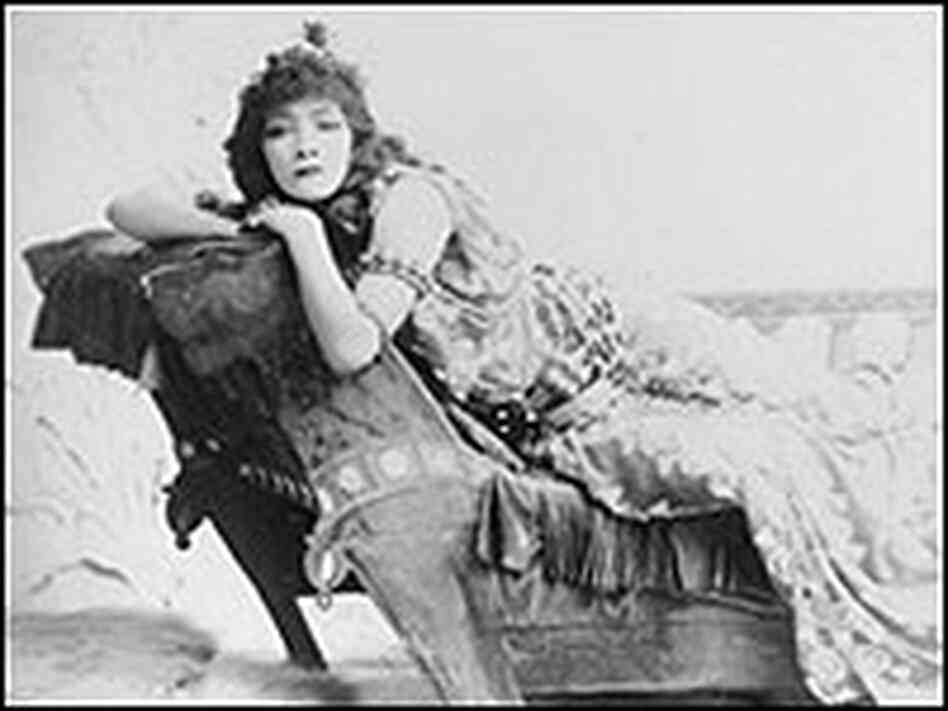 Sarah Bernhardt reclines on a divan playing the role of Cleopatra in an 1880 production.